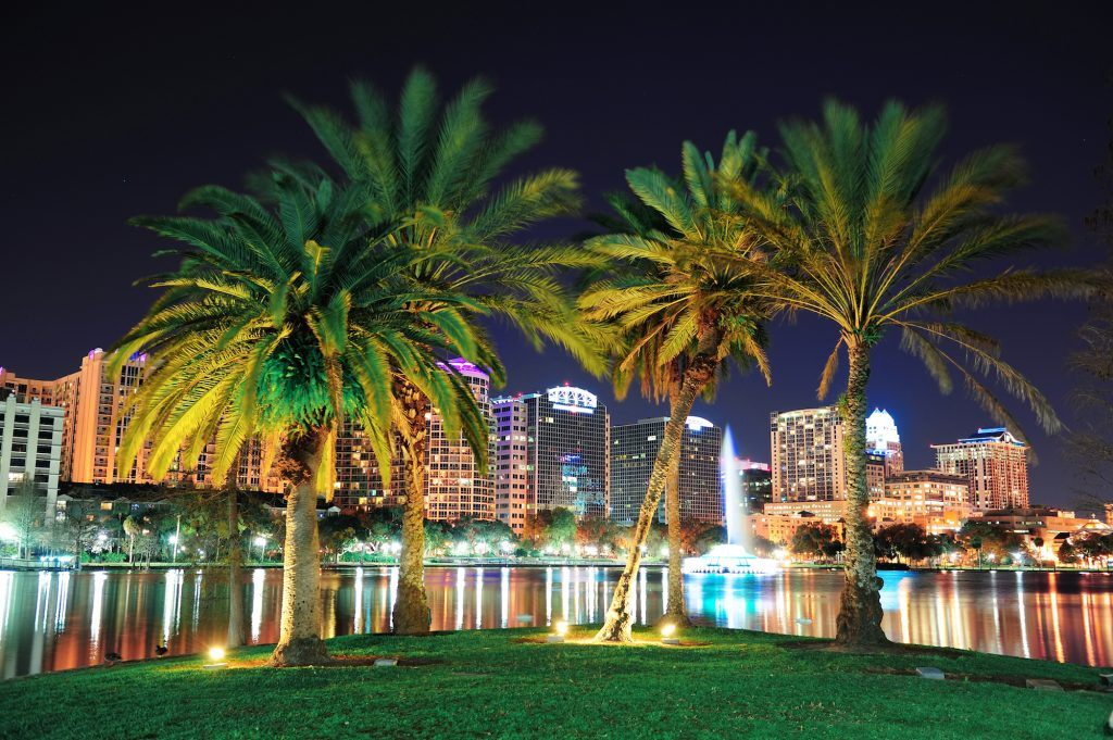 Orlando downtown skyline panorama over Lake Eola at night with urban skyscrapers, tropic palm tree a
