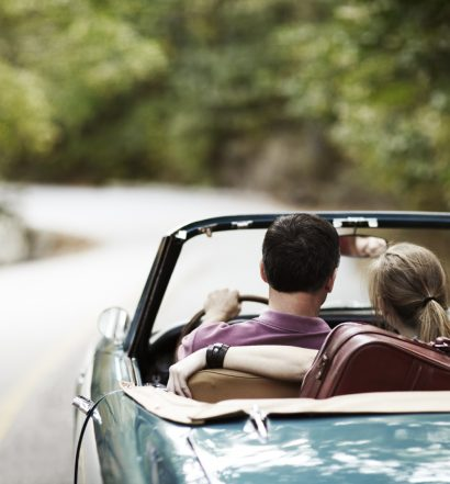 Couple taking a road trip in vintage convertible.