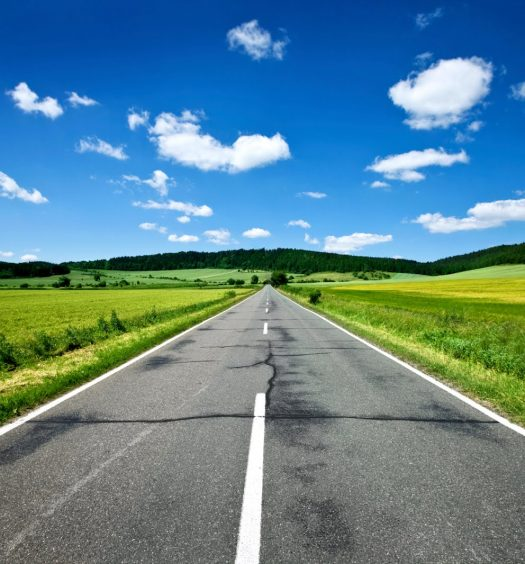 blue skies and green grass driving down the open road