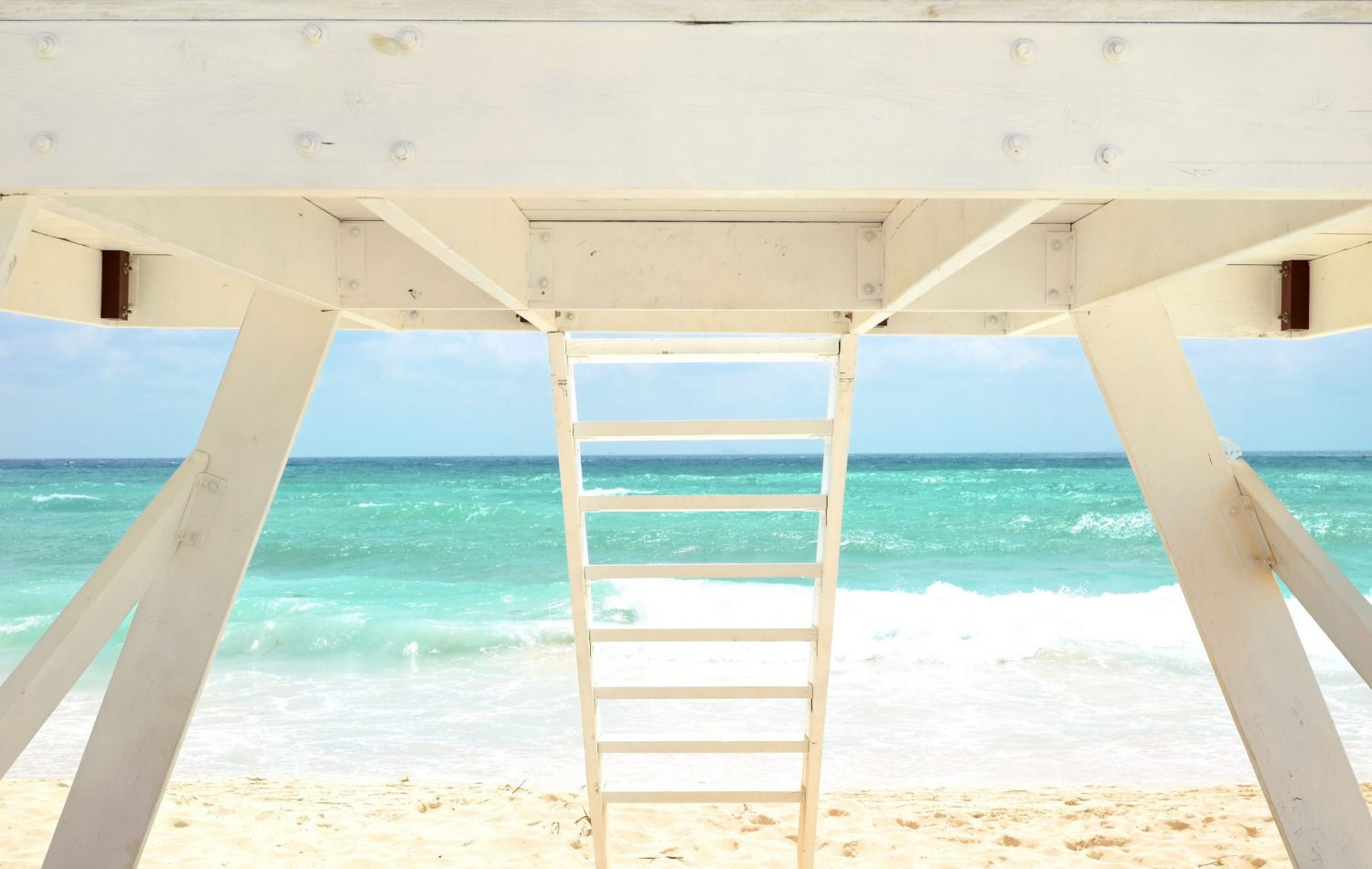 White Lifeguard house on a sandy beach in summer with turquose ocean and blue cloudy sky