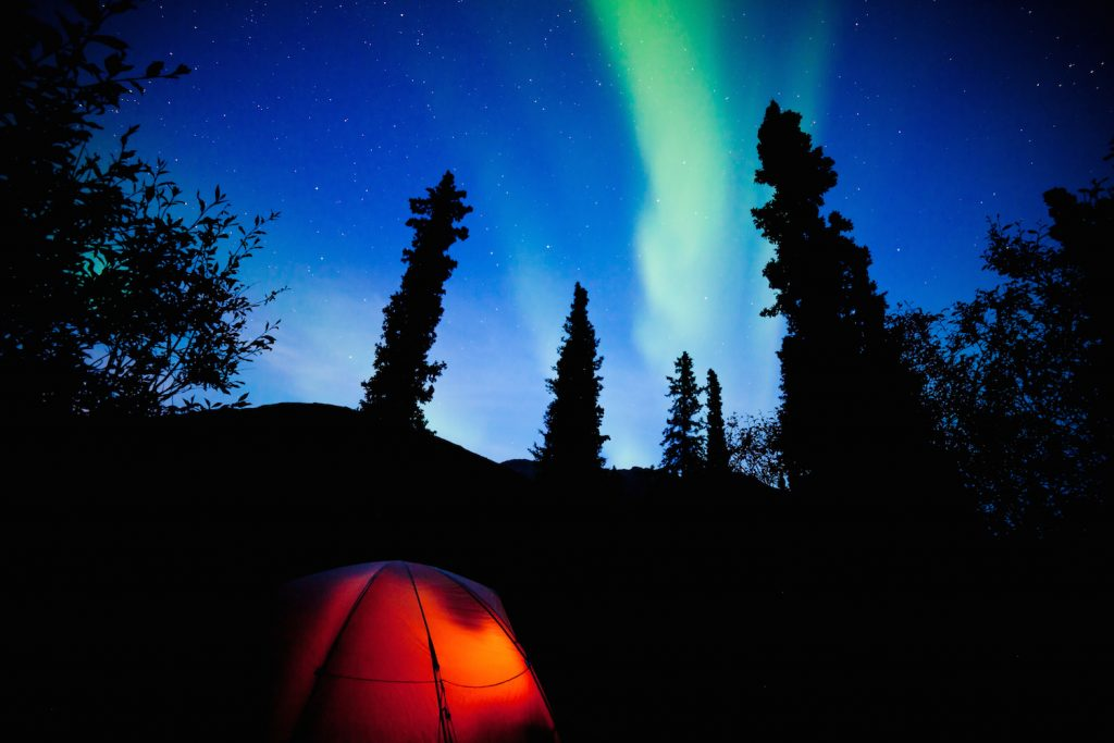 Orange Taiga Tent Glow Under Northern Lights Flare