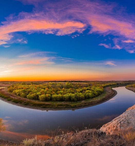 A panoramic view of Badlands National Park against a sunset.