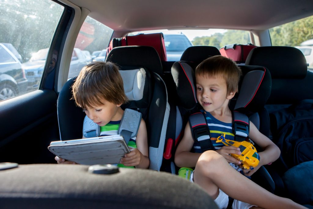 Two Boys In Children Car Seats, Traveling By Car And Playing With Toys And Tablet