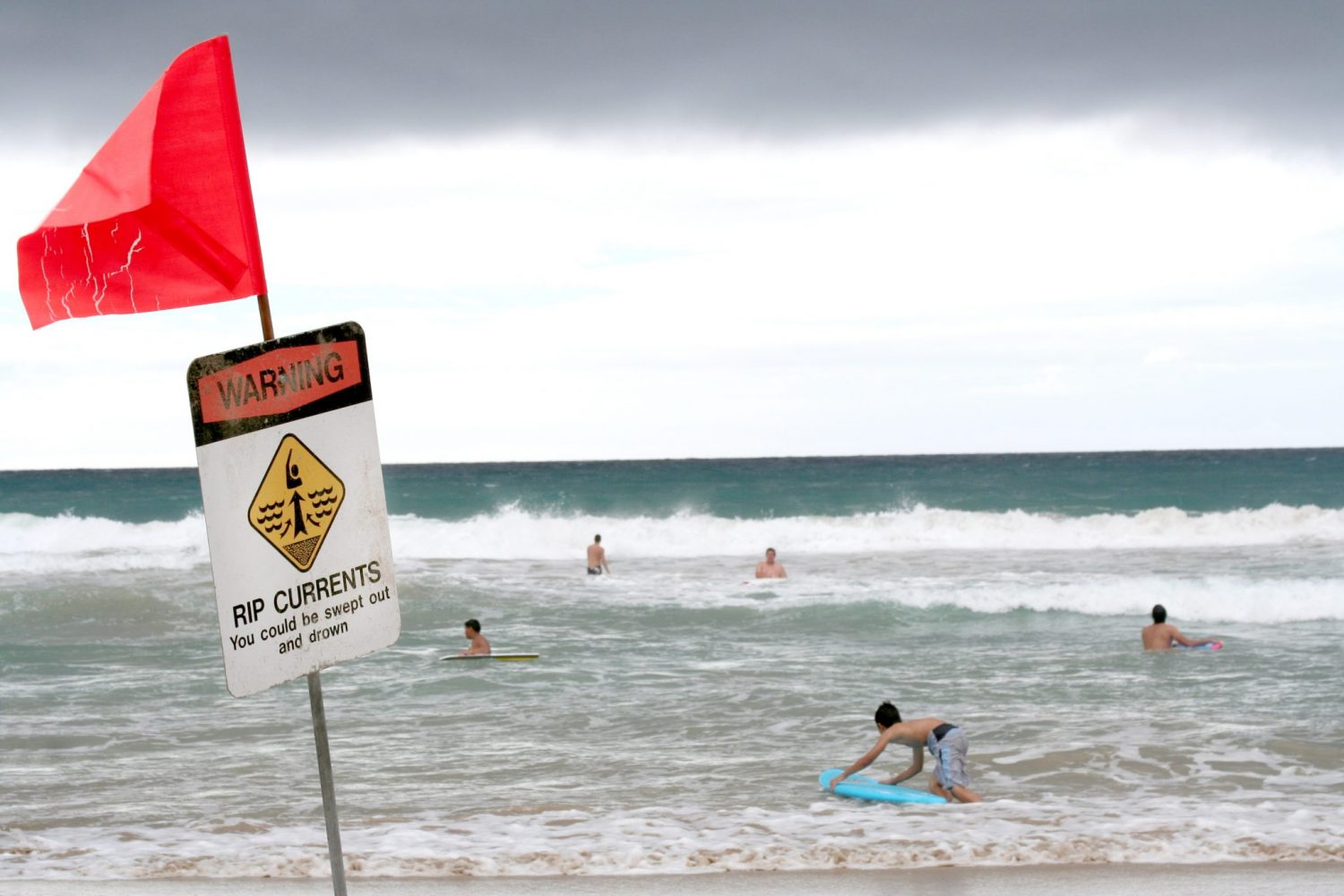 Swimmers are out in the ocean despite the warnings of rip currents.