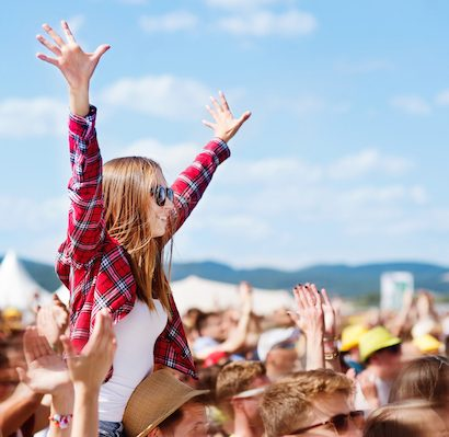 Teenage girl on friend's shoulders at music festival