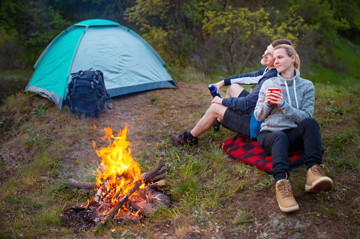 Young happy couple camping in forest.
