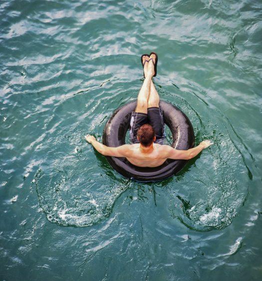 man floating in tube in river
