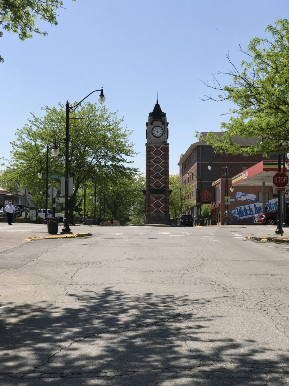Street shot with clock building and signs in Campus town, Iowa.