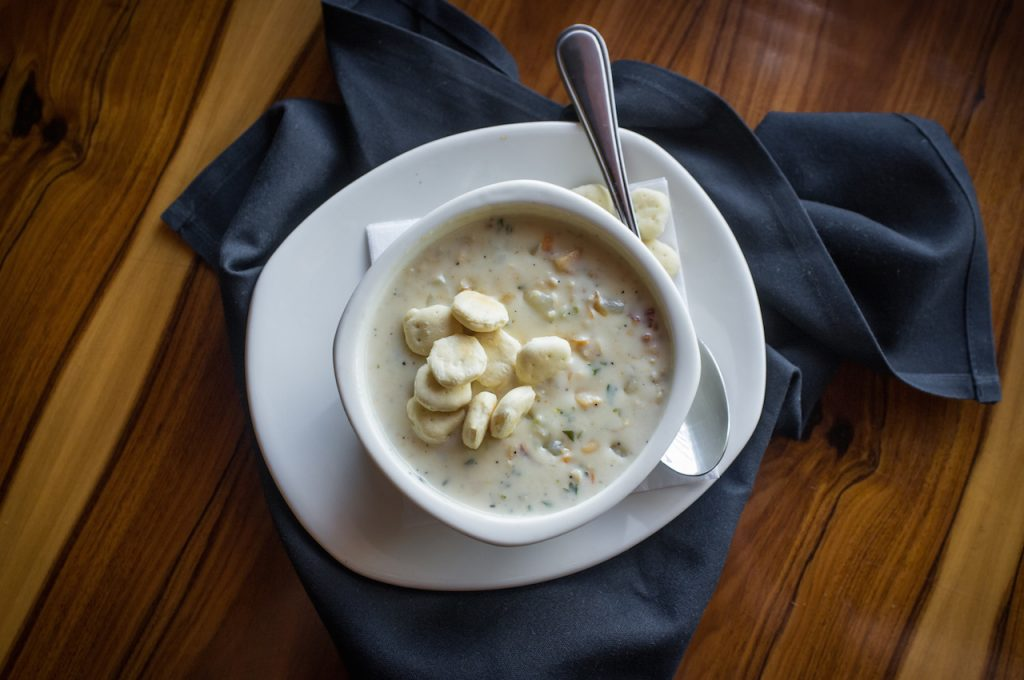a cup of new england clam chowder, topped with crackers, on a plate with a spoon and blue napkin