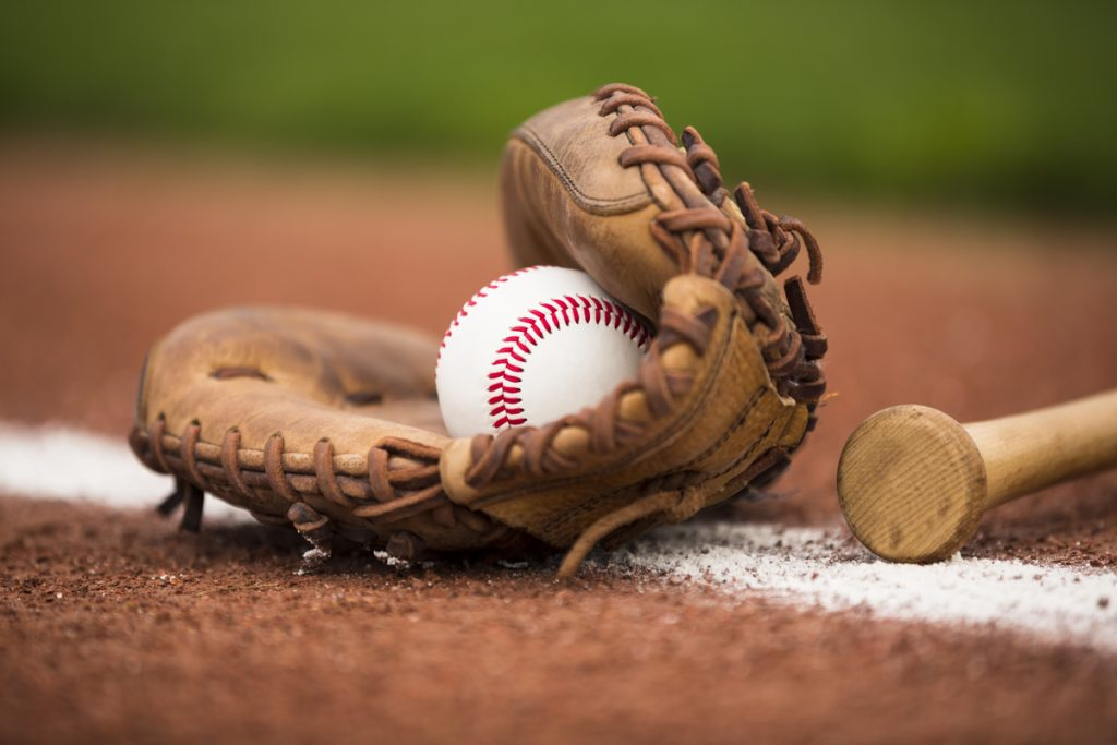 baseball inside of a glove, on the ground , next to a bat.
