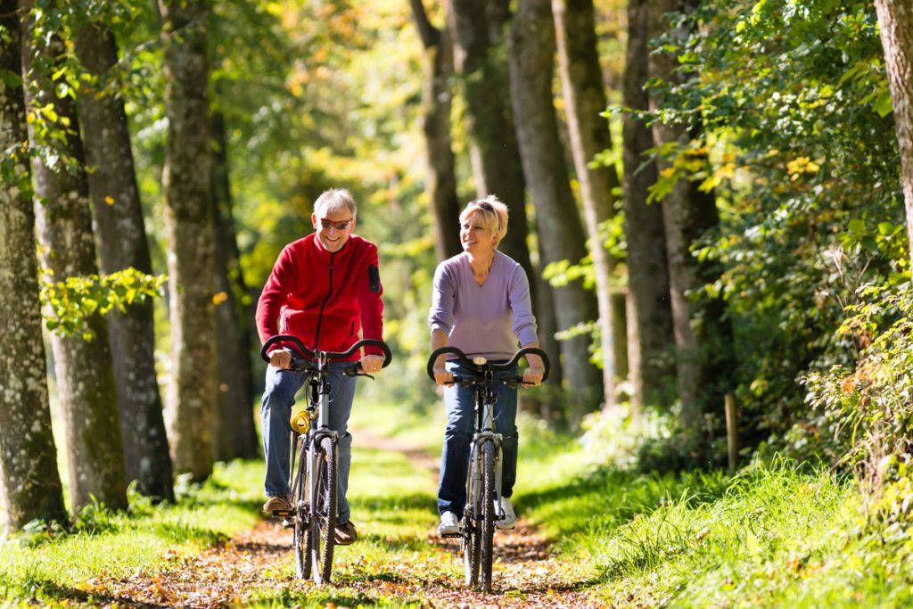 Older man and woman biking through a bicycle path near trees and leaves