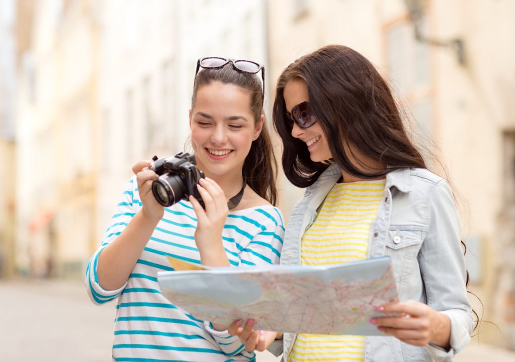 Two young attractive women are touring a new city, with a camera and map in their hands
