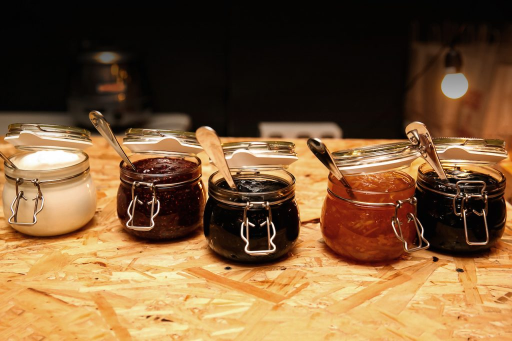 Glass jars with different kinds of jam and berries on wooden table, Homemade jars of fruits jam on rustic wooden background