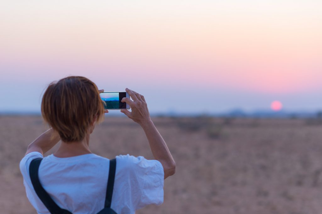 Woman tourist with her smart phone, photographing the romantic desert sunset