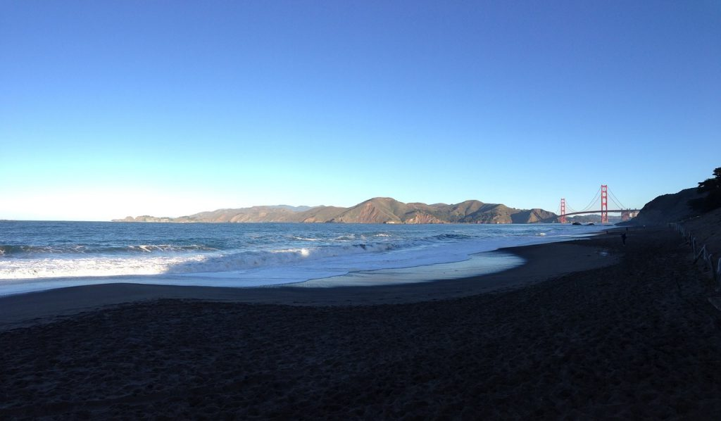 Waves and water blowing in the wind on Baker Beach with the Golden Gate Bridge in the distant background