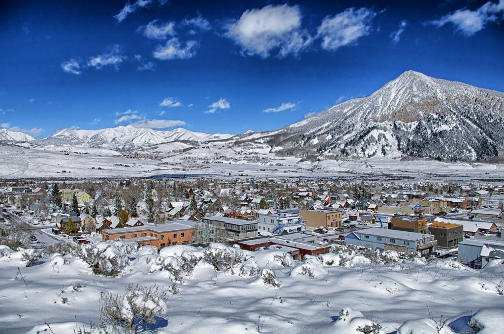 Crested Butte, Colorado, townview with snow covering everything and mountains in the background