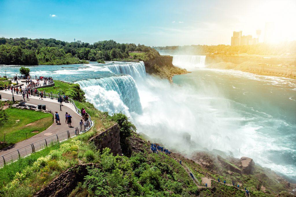 American side of Niagra falls NY USA. Tourists enjoying beautiful view to Niagra Falls during hot sunny summer day.