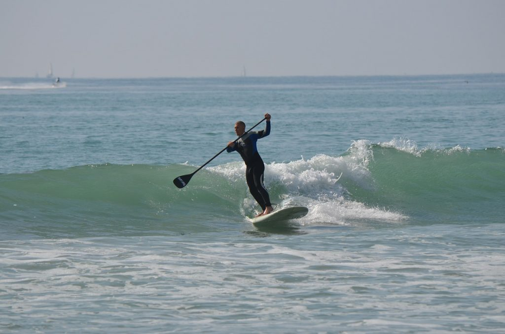 man wearing a wetsuit paddle surfing in the ocean
