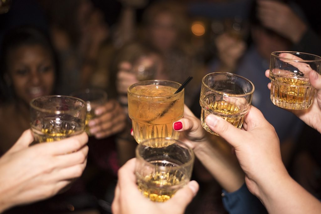 a bunch of friends out drinking holding up their whiskey glasses for a cheers