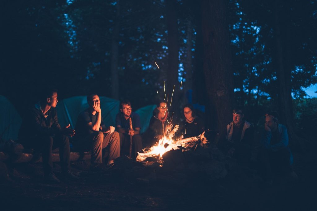 group of friends camping and sitting around a bonfire at nighttime